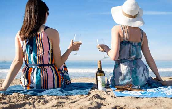 Women drinking Kris Pinot Gris wine on the beach